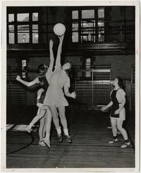 Basketball game in Blanchard Gymnasium, with Doris Busterfield tapping the ball