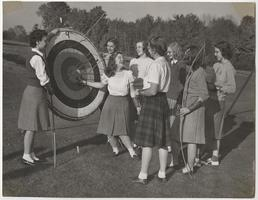 Students in archery class, including Lee Holcombe '49 and Joanne Main on either side of target, and Alice Everett '50 in center