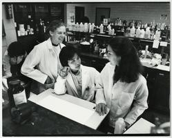 Professor Lillian Hsu (center) talking with students in a laboratory of the Biological Sciences Department