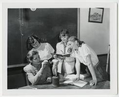 Four students studying a sculpture