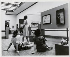 Three students evaluating a picture in the Dwight Hall gallery, for an art course at Mount Holyoke