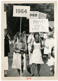 Members of the Class of 1964 carrying signs in the Alumnae Parade at their 15th reunion, with Class of 1969 in the background
