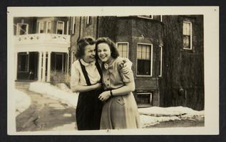 Two young women laughing and embracing outside of Safford Hall.