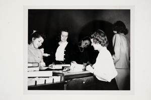 Patricia (Pat) Taitt '48, Kenny Galt '49, and Pauline (Polly) McKinley '48 working with a staff member
