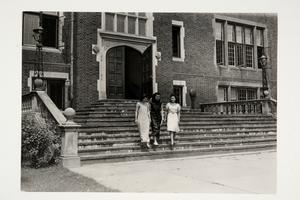 Three international students walking down the steps of Skinner Hall, including possibly Man-ye Chang '43 from Shanghai, China, on the far right