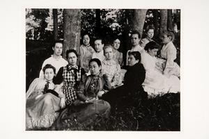 Group including international students seated in grove of trees