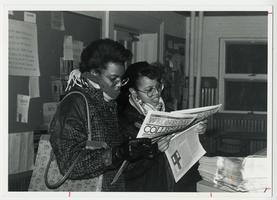 "Two students reading the ""Collegian"" newspaper"