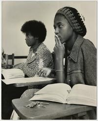 Two students in class, listening to a lecture