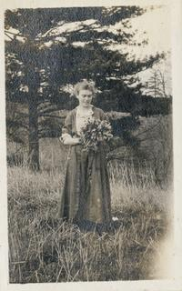 Marion Blake as a student, holding flowers, standing with a tree and a grassy hillside in the background