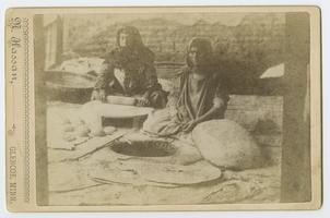 "Two peasant women using a ""toneer"" to bake bread during the time of Charlotte and Mary A. C. Ely in Turkey"