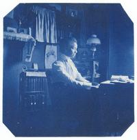 Otelia Cromwell (Class of 1900) sitting at a desk