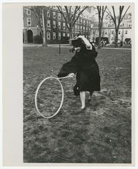 Student hanging onto mortarboard while hoop rolling